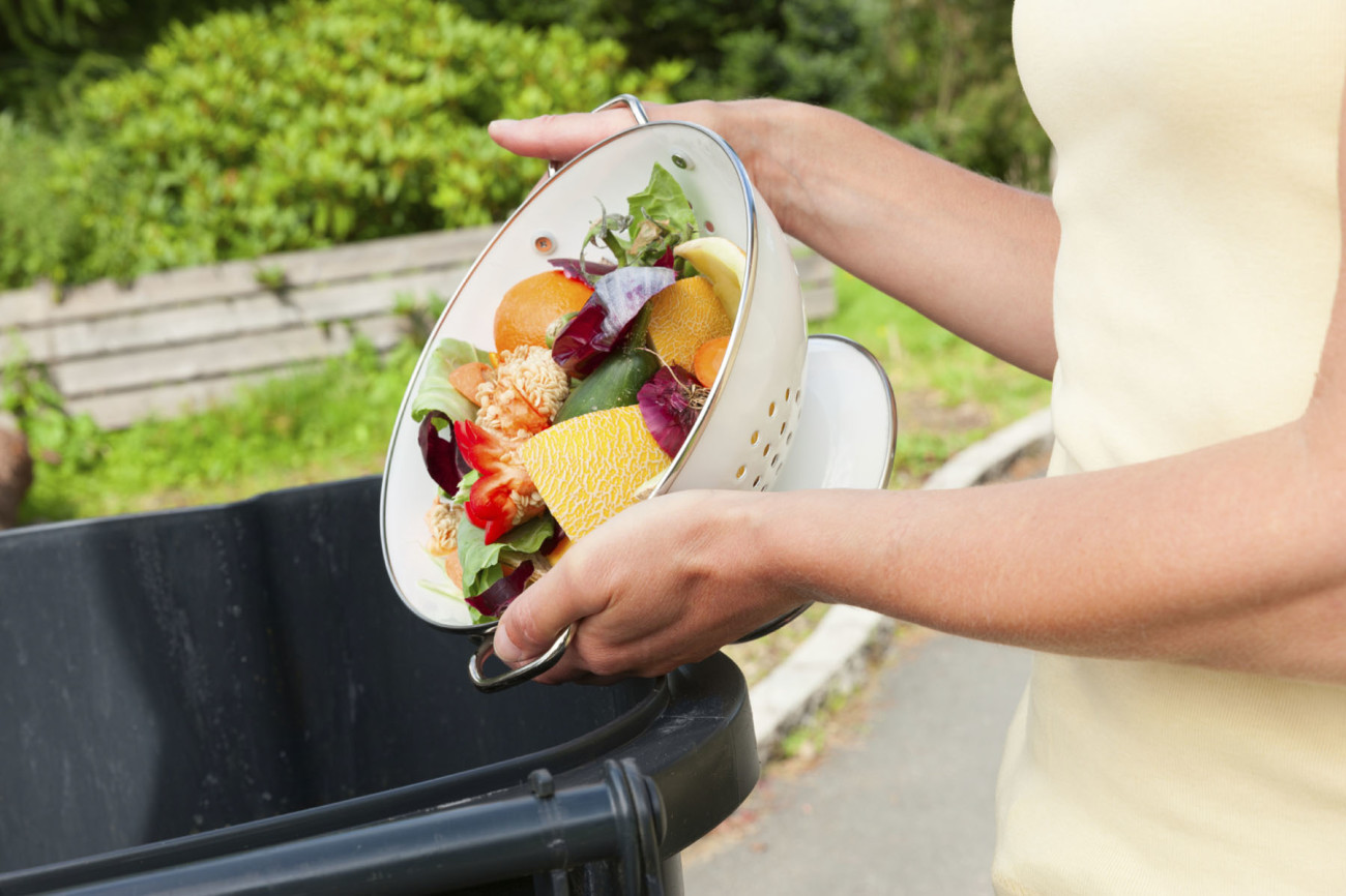 Unrecognizable woman emptying a collander of fruit and vegetable waste into a black plastic bin.