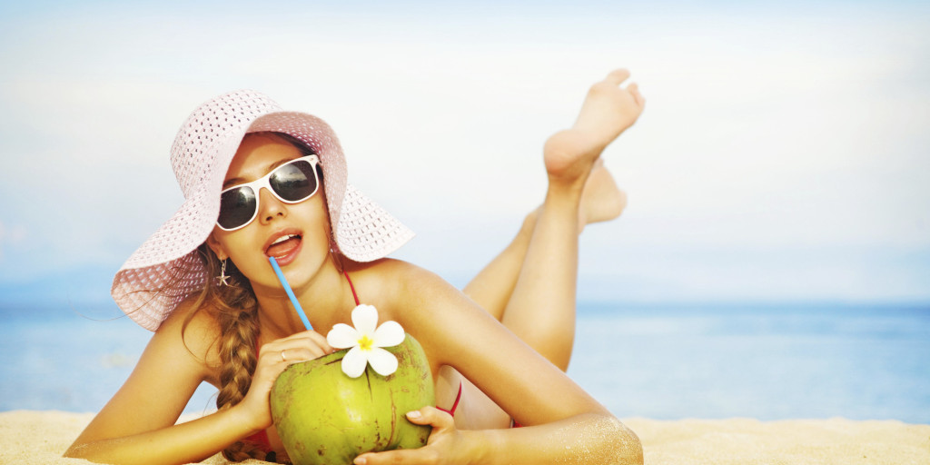 Young woman in pink swimsuit with coconut cocktail